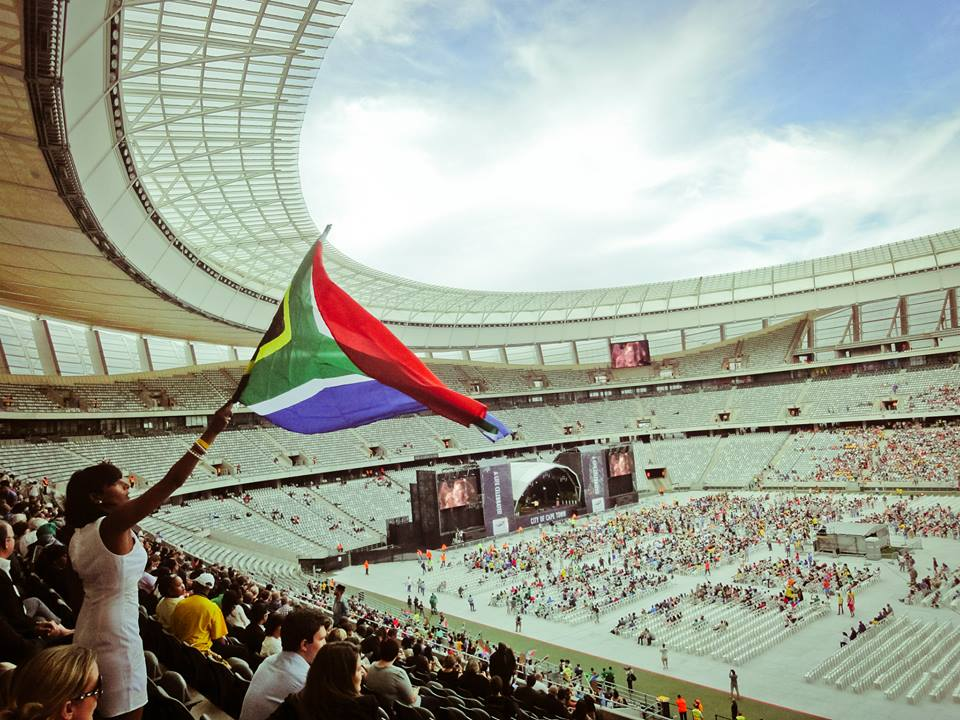 Threats facing South Africa (a woman in a stadium waving a South African flag)
